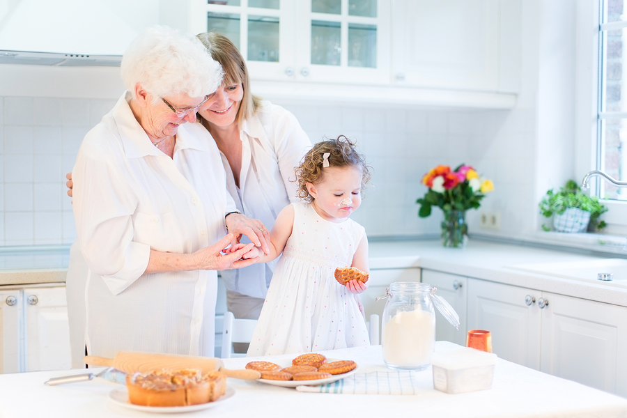 Happy Young Woman Baking A Cake With Her Senior Mother And Cute